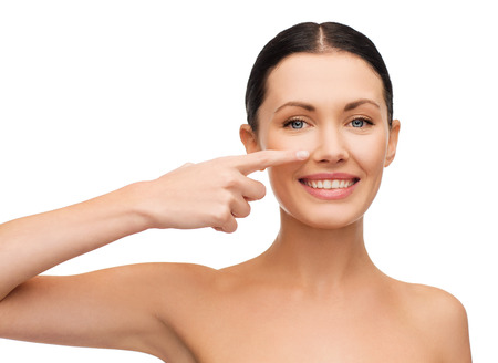 plastics: health, spa and beauty concept - clean face of beautiful young woman pointing to her cheek