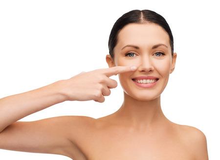 nariz: la salud, el spa y el concepto de belleza - la cara limpia de la hermosa mujer joven que se�ala a la mejilla