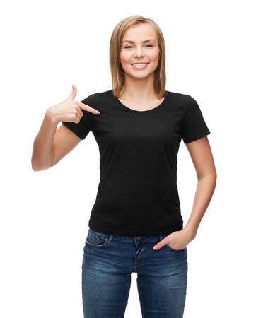 De t-shirt design, gelukkige mensen concept - glimlachende vrouw in lege zwarte t-shirt die haar vinger naar zichzelf