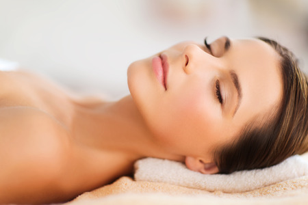 women body: beauty and spa concept - beautiful woman in spa salon lying on the massage desk