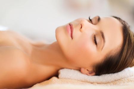 tratamiento facial: la belleza y el concepto de spa - bella mujer en salón del balneario sobre el escritorio de masaje