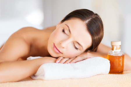 salon and spa: beauty and spa concept - happy woman in spa salon lying on the massage desk Stock Photo