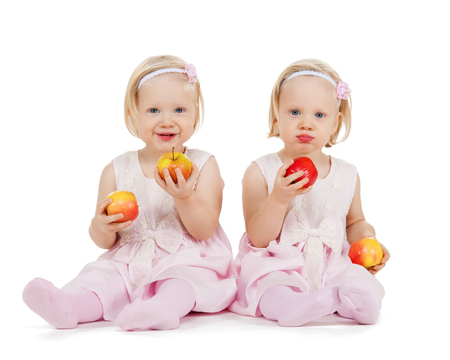 children, food and twins concept - two identical twin girl playing with apples photo