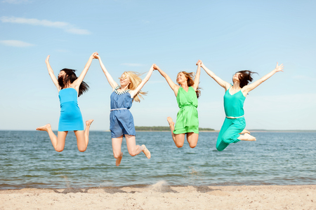 party dress: summer holidays and vacation concept - smiling girls jumping on the beach