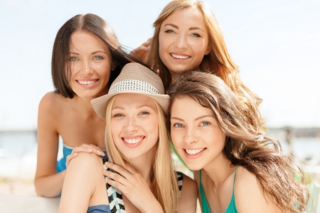 open air: summer holidays and vacation concept - group of smiling girls in cafe on the beach