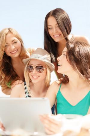 cafe internet: vacaciones de verano, vacaciones, internet y el concepto de la tecnología - sonriente a las niñas que buscan en tablet pc en la cafetería Foto de archivo