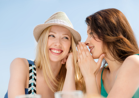 gossip: summer holidays and vacation concept - girls gossiping in cafe on the beach