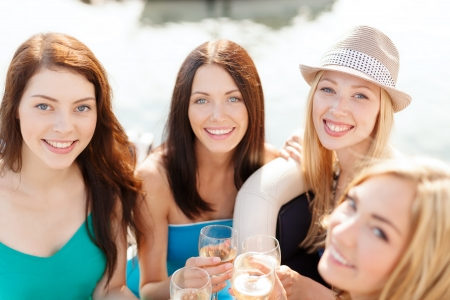 summer holidays, vacation and celebration concept - smiling girls with champagne glasses photo