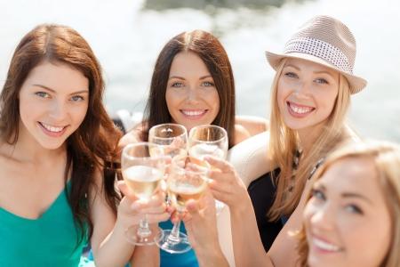 despedida de soltera: niñas sonriendo con vasos de champán - las vacaciones de verano, vacaciones y celebre concepto Foto de archivo