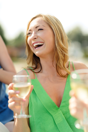 summer holidays, vacation and celebration concept - laughing woman with wine glass photo