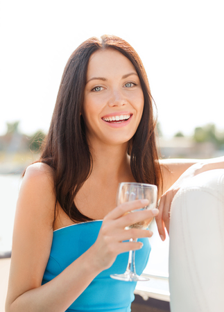 summer holidays, vacation and celebration concept - laughing girl with champagne glass photo