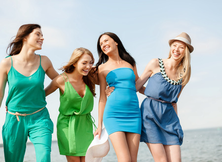 blue dress: summer holidays and vacation concept - smiling girls walking on the beach