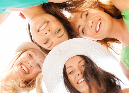 looking down: summer holidays and vacation concept - faces of girls looking down and smiling