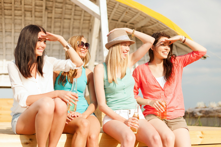 bachelorette party: summer holidays and vacation concept - smiling girls with drinks on the beach searching for someone or something Stock Photo