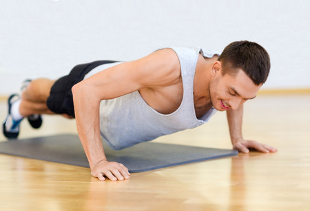 musculine: fitness, sport, training, gym and lifestyle concept - smiling man doing push-ups in the gym or at home