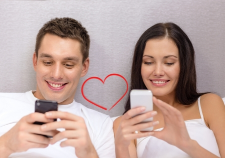 bedroom bed: hotel, travel, relationships, technology, intermet and happiness concept - smiling couple in bed with smartphones