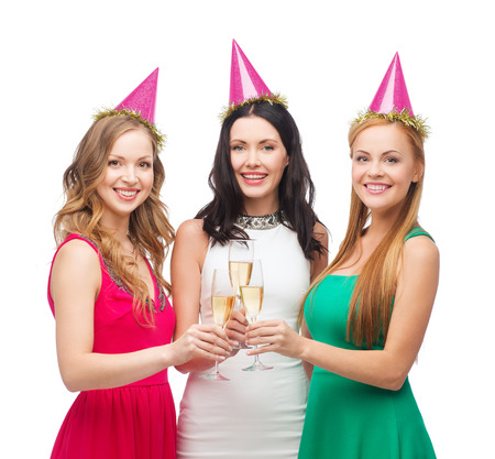 celebration, drinks, friends, bachelorette party, birthday concept - three smiling women wearing pink hats with champagne glasses photo