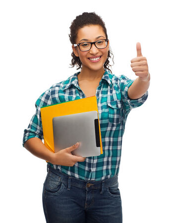education, technology and people concept - smiling female african american student in eyeglasses with folders and tablet pc photo