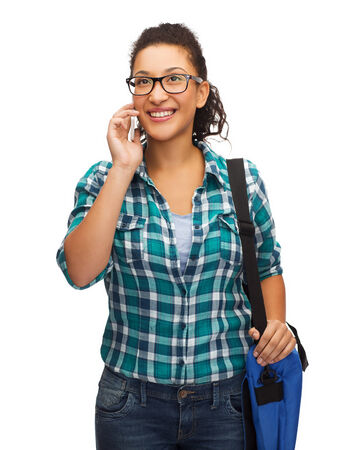 education, technology and people concept - smiling female african american student in eyeglasses with smartphone and bag photo
