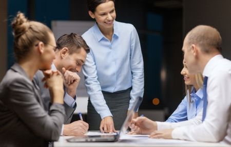 female boss: business, technology and office concept - smiling female boss talking to business team