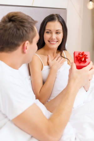 romantic room: hotel, travel, relationships, holidays and happiness concept - man giving woman little red gift box