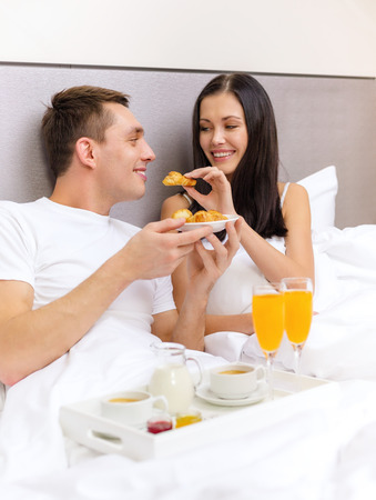 bed and breakfast: hotel, travel, relationships and happiness concept - smiling couple having breakfast in bed in hotel room Stock Photo