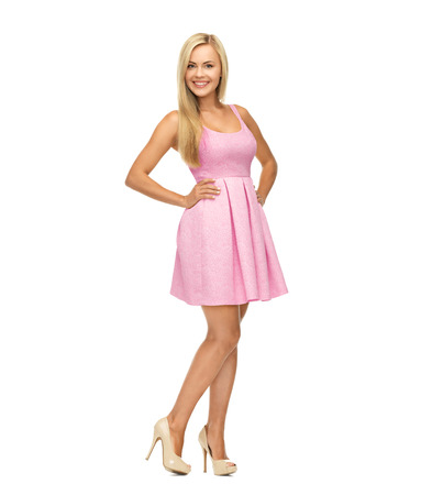 beauty, fashion and happy people concept - young woman in pink dress and high heels photo