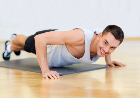 home gym: fitness, sport, training, gym and lifestyle concept - smiling man doing push-ups in the gym or at home