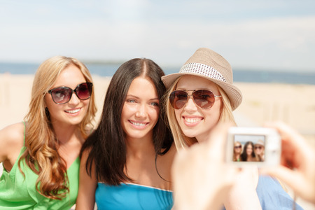digi: summer holidays and vacation concept - smiling girls taking photo with digital camera in cafe on the beach