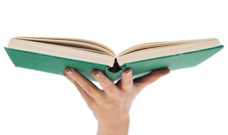 education and book concept - close up of woman hand holding open green book photo