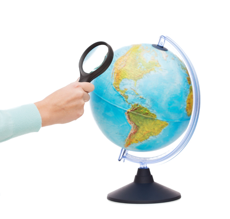 travel, earth, geography and research concept - close up of woman hand holding magnifying glass over earth globe photo