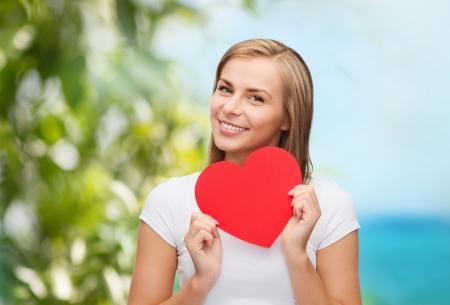 buena salud: mujer sonriente en la camiseta blanca con el coraz�n - concepto de felicidad, salud, vacaciones y amor