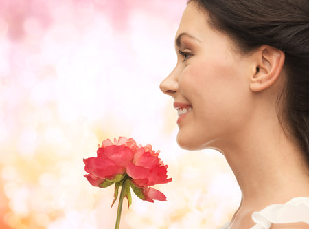 picture of smiling woman smelling flower photo