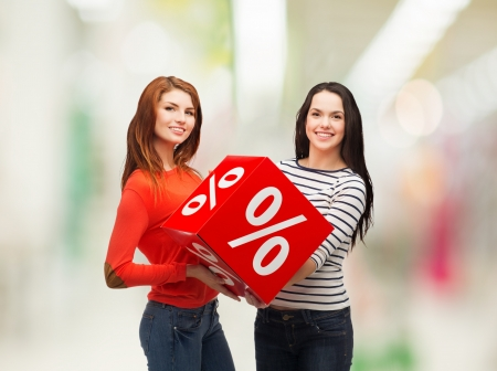 shopping, sale, mall and gift sconcept - two smiling teenage girls with percent sign on red box at shopping mall photo