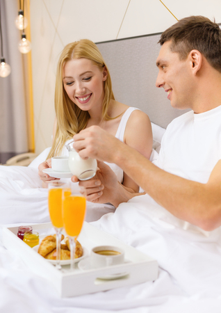 breakfast room: hotel, travel, relationships and happiness concept - smiling couple having breakfast in bed in hotel room Stock Photo