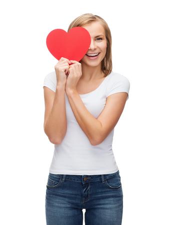 geluk, t-shirt design, gezondheid en liefde concept - glimlachende vrouw in lege witte t-shirt met die half gezicht met hart Stockfoto
