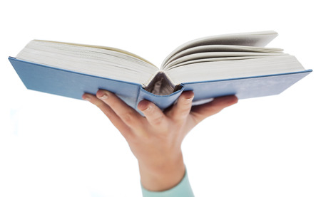 education and book concept - close up of woman hand holding open blue book photo