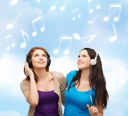 music and technology concept - two smiling teenagers with headphones looking up photo