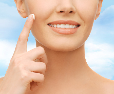 lovely woman: healthcare and beauty concept - beautiful woman applying moisturizing cream