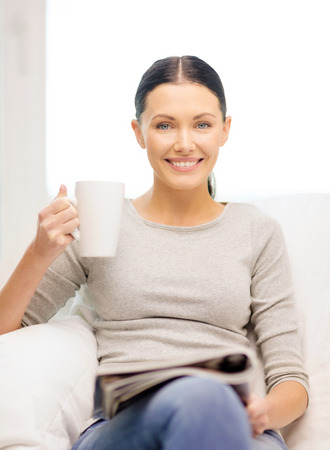 leasure: home and leasure concept - smiling woman with cup of coffee or tea reading magazine at home Stock Photo