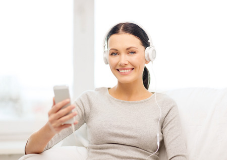 home, technology, communication and internet concept - woman sitting on the couch with smartphone and headphones at home photo