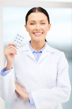 healthcare, pharmacy and medicine concept - smiling young doctor with pills in cabinet