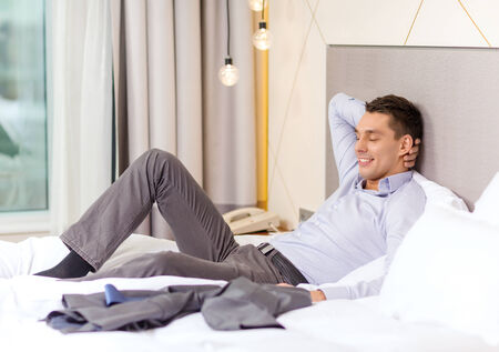 business, technology, internet and hotel concept - happy businesswoman lying in bed in hotel room Stock Photo - 25546119