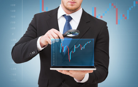 forex: technology, internet and business concept - businessman holding magnifying glass over tablet pc computer