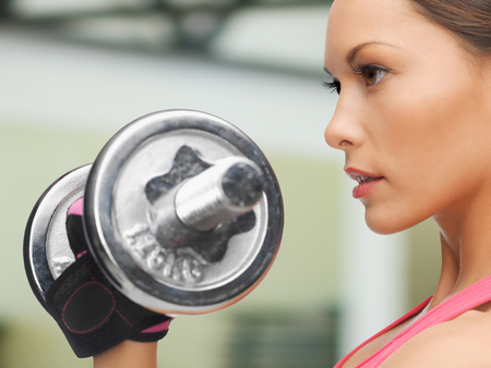 woman lifting weights: fitness, sport, training, gym and lifestyle concept - sporty woman with dumbbell in gym Stock Photo