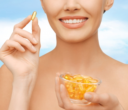 omega 3: healthcare and beauty concept - beautiful woman with omega 3 vitamins Stock Photo