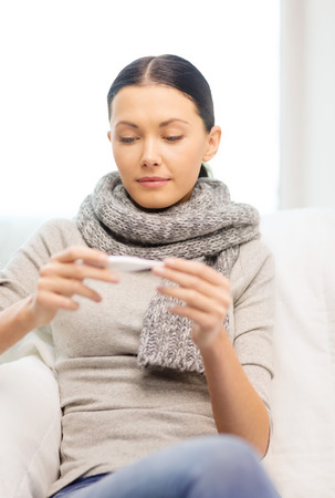 healthcare, home and medicine concept - ill woman with flu at home looking at thermometer photo