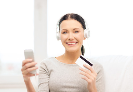home, technology, online shopping and internet concept - woman sitting on the couch with smartphone, credit card and headphones at home photo