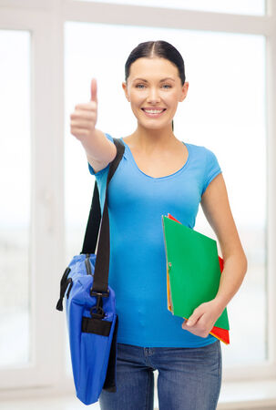 education and school concept - smiling female student with folders and bag at school showing thumbs up photo