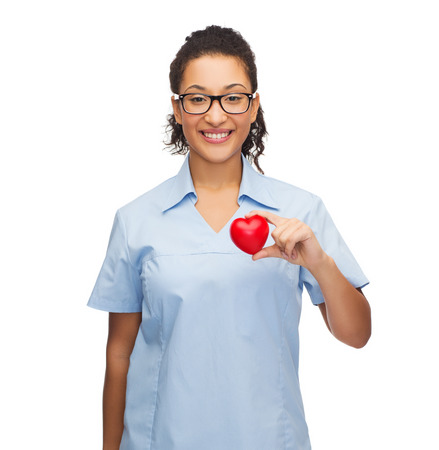 glass heart: healthcare and medicine concept - smiling female african american doctor or nurse in eyeglasses with heart Stock Photo